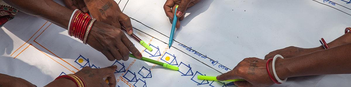 Hände zeigen mit Stiften auf Notfallplan