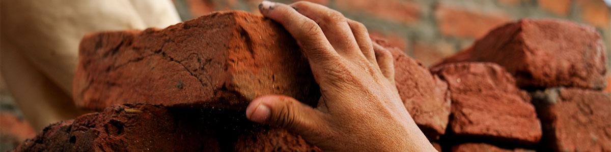 Hand mit Ziegelstein beim Bauen