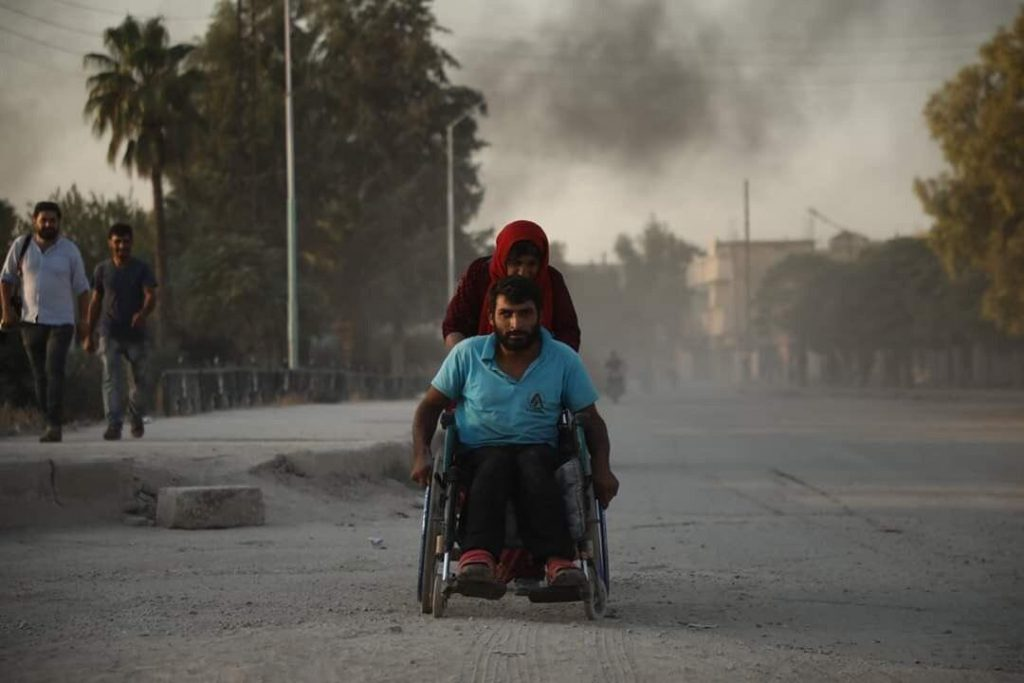 Mann im Rollstuhl wird von Frau über eine Straße in Syrien geschoben. Im Hintergrund ist Rauch